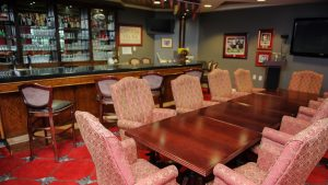 Capstone Village lounge with glassware, woodgrain bar, bar stools and table set with ten arm chairs