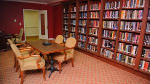 Capstone Village library with bookcases lining one wall and table set with four tan chairs