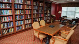 Capstone Village library with bookcases lining one wall and two tables set with chairs