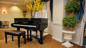 Capstone Village parlor baby grand piano and green topiary