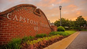 Red brick Capstone Village entry sign at sunset