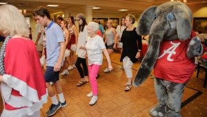 Capstone Village retirees, guests and University of Alabama cheerleaders line dance with Big Al