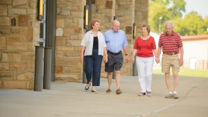Two smiling Caucasian retiree couples stroll along a path outside a brick building