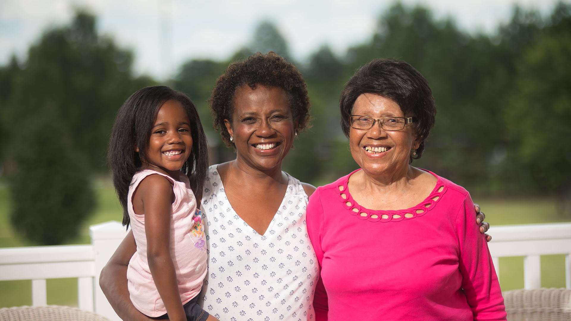Three generations of black women smile while outside