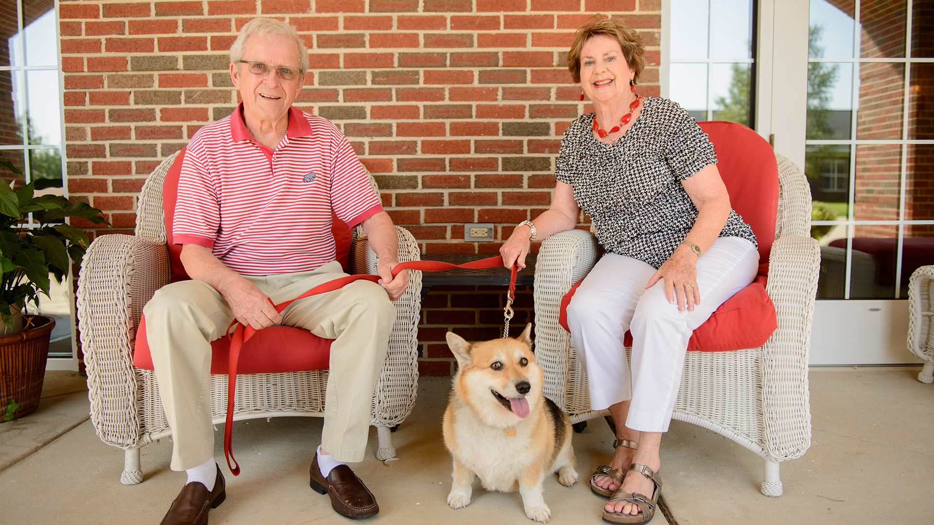 Smiling retiree couple relax outside Capstone Village in wicker chairs with their dog