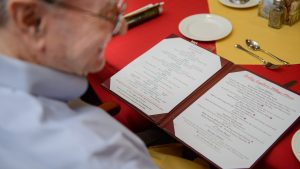 Capstone Village retiree reviews Capstone Village menu on table set with red tablecloth and silverware