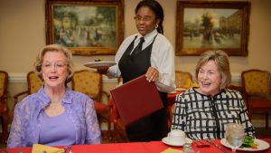 Two Caucasian female retirees wait to receive menus and salad from an African-American server