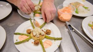 Tom uses a spoon to sauce six servings of crabcakes with remoulade and asparagus tips