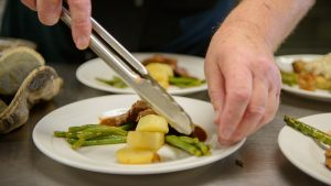 Capstone Village sous chef, Tom, uses tongs to plate four servings of pork loin, asparagus and pineapple on white china