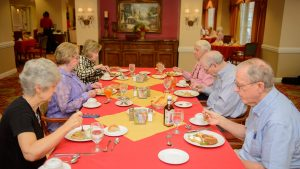 Three Caucasian retiree couples enjoy a meal in Capstone Village's dining room