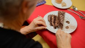 A female retiree in a black blouse enjoys a slice of chocolate cake at Capstone Village