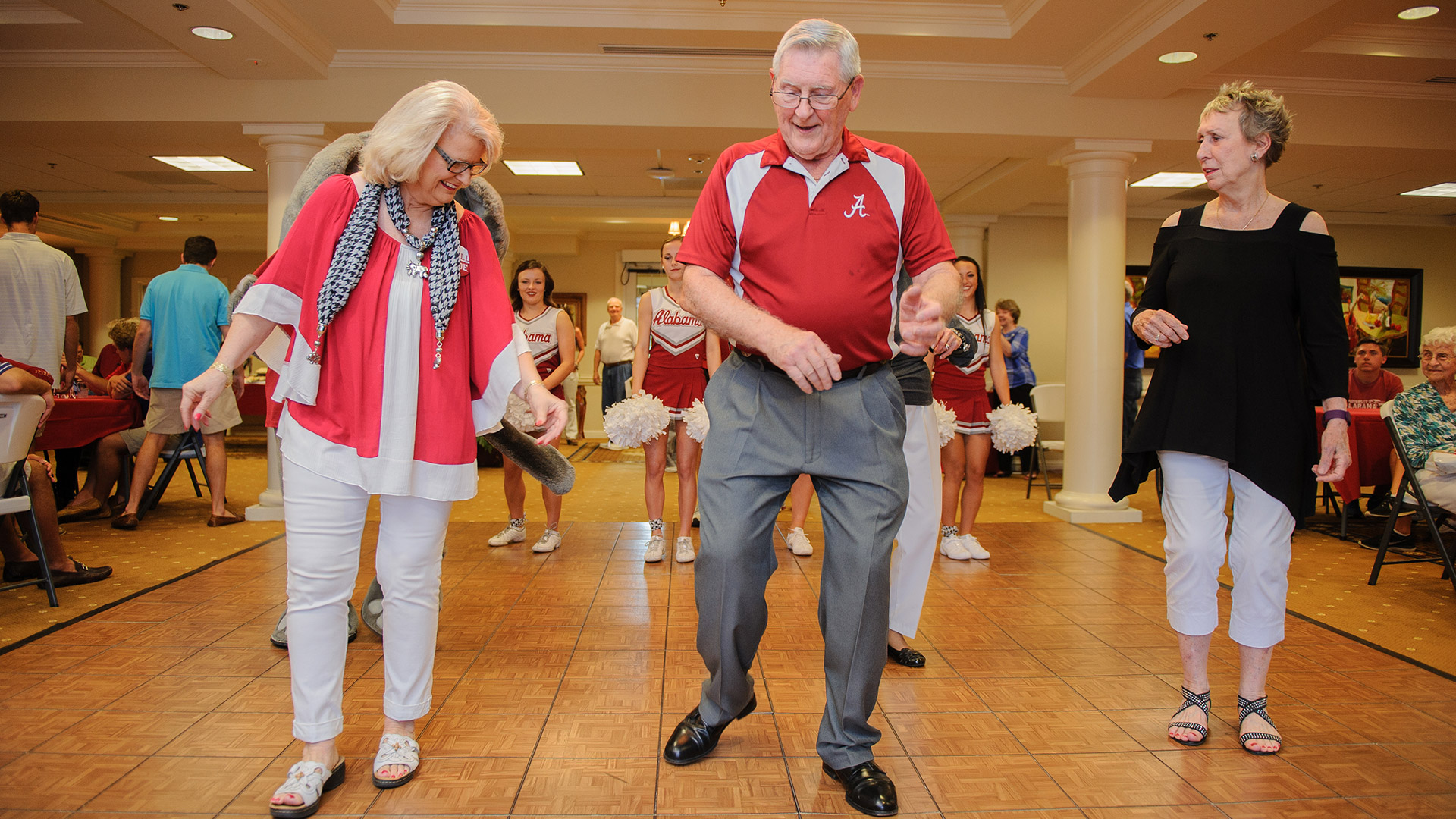 Two female and one male Capstone Village residents dance on a hardwood floor