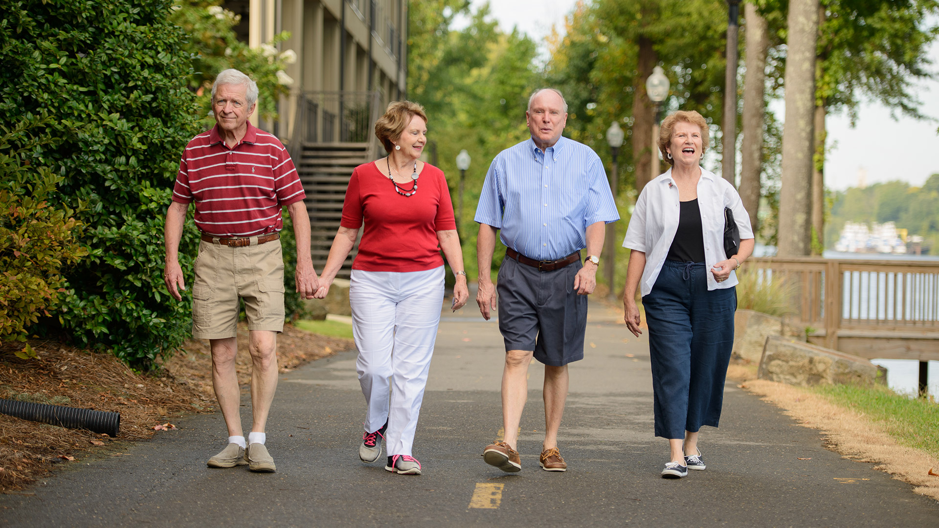Four people walking together outside on a sunny day