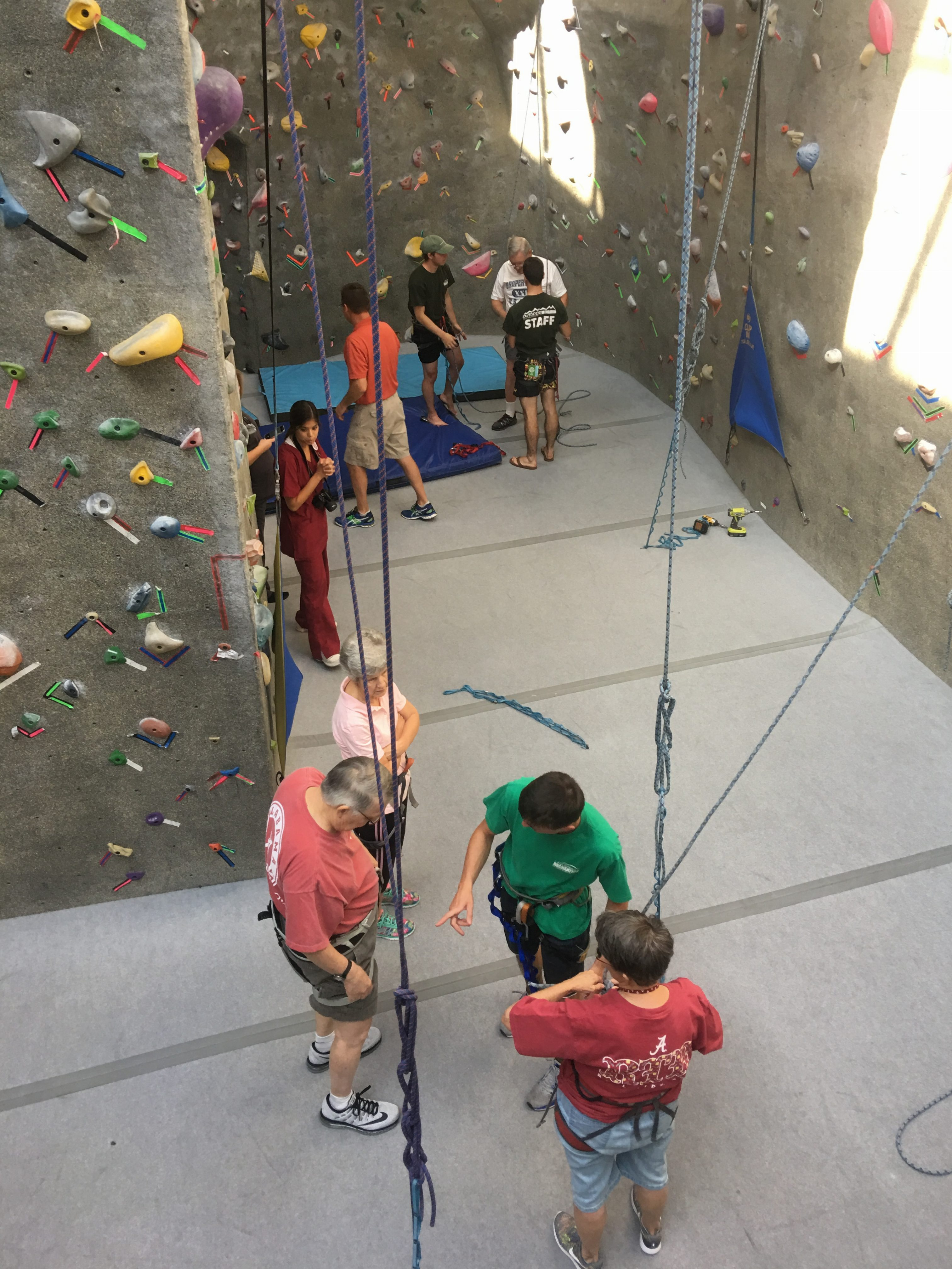 A group of people getting ready to climb an indoor rock wall