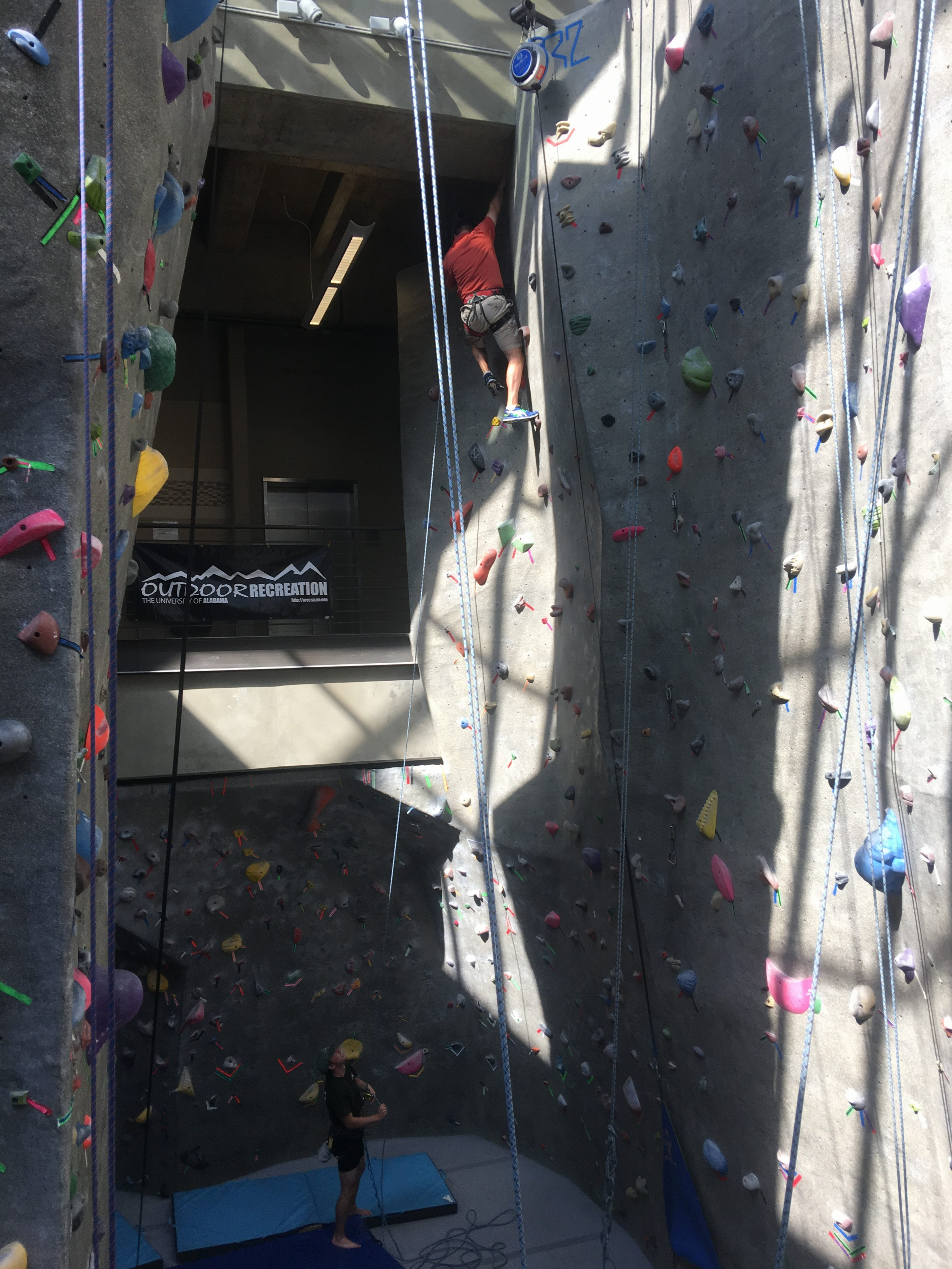 A man climbing to the top of the rock wall
