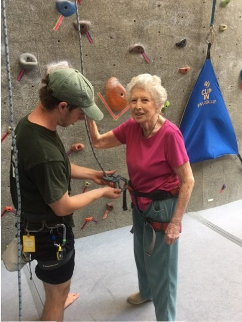 A woman starts her climb with the help of a man