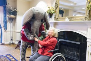 Big Al helps a woman in a wheelchair in front of a fireplace