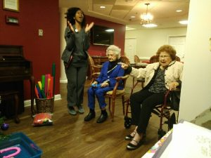 A woman jumping high into the air as older residents watch