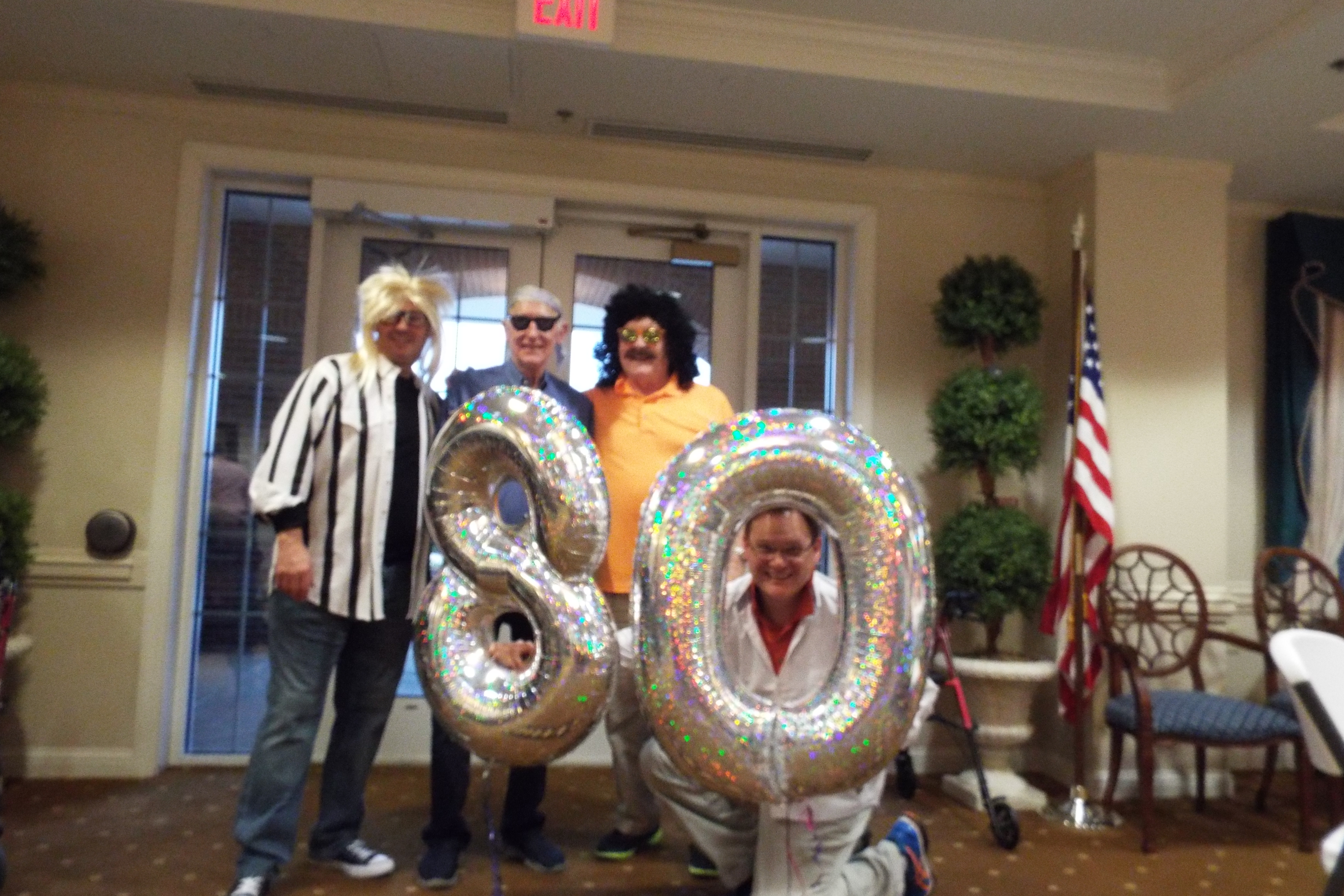 four residents pose with 80 balloon