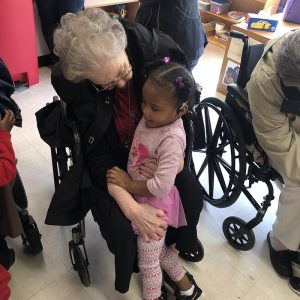 An older lady in a chair walks to a young girl