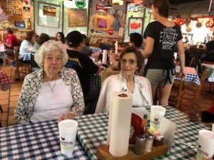 Two ladies sit inside a busy restaurant