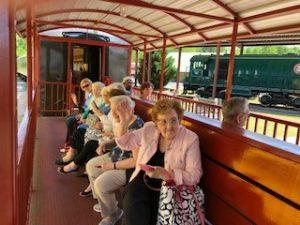 A group sits in an open air train car