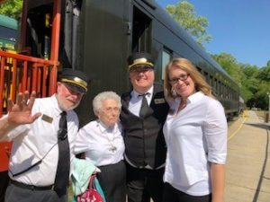 two ladies pose with two train conductors outside