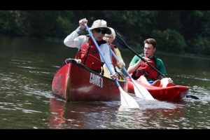 Three people canoe down the river